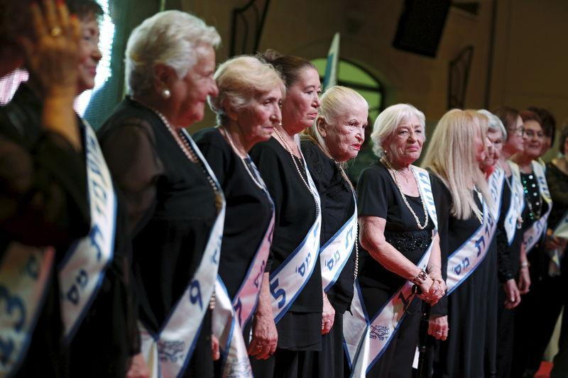 Holocaust survivors stand on a stage during a beauty contest for survivors of the Nazi genocide in Haifa